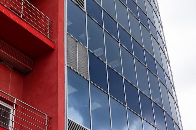 Moderne business center glasfassade und orange wände mit balkon und himmel oberfläche
