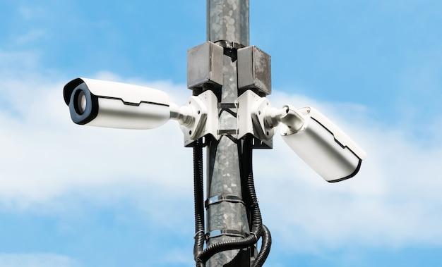 Moderne cctv-kameras auf strommast mit hellem himmelhintergrund