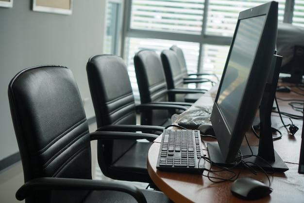 Moderne computer, dual-screen-monitore und schwarze stühle.