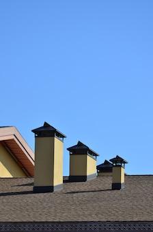 Moderne dacheindeckung und dekoration von schornsteinen. flexibles bitumen oder schieferschindeln.