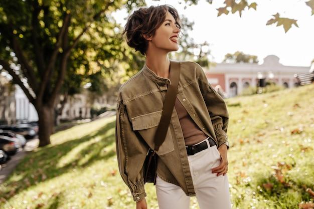 Moderne dame in jeansjacke mit handtasche, die draußen wegschaut. wellenhaarige frau mit roten lippen in weißen hosen, die draußen lächeln.