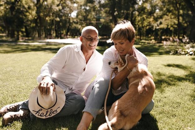 Moderne dame mit blonden kurzen haaren im weißen hemd, das hund umarmt und auf gras mit mann in brillen in weißen kleidern im freien sitzt.