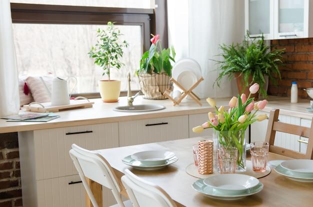 Moderne designküche. esstischgedeck mit blumenvase
