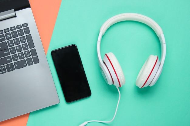 Moderne digitale geräte und zubehör. laptop, smartphone, kopfhörer auf farbigem hintergrund. pastellfarbentrend. draufsicht.