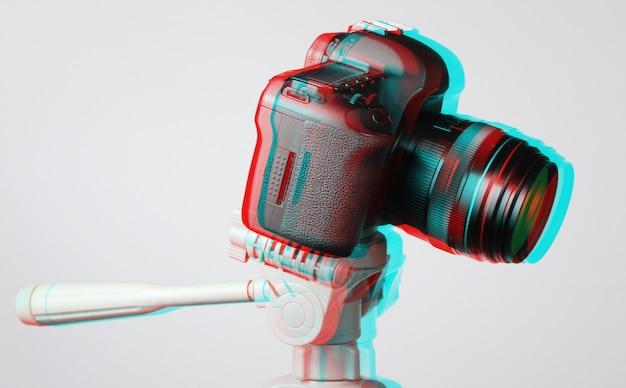 Moderne digitalkamera mit einem stativ auf grauem hintergrund. glitch-effekt