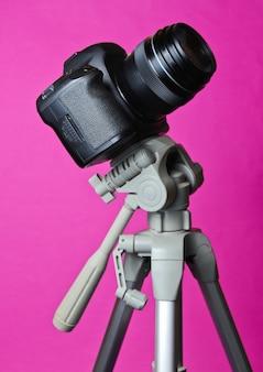 Moderne digitalkamera mit einem stativ auf rosa tisch. astrofotografie