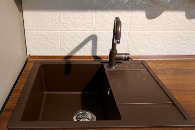 Moderne dunkelbraune quadratische spüle auf der oberfläche des küchensets