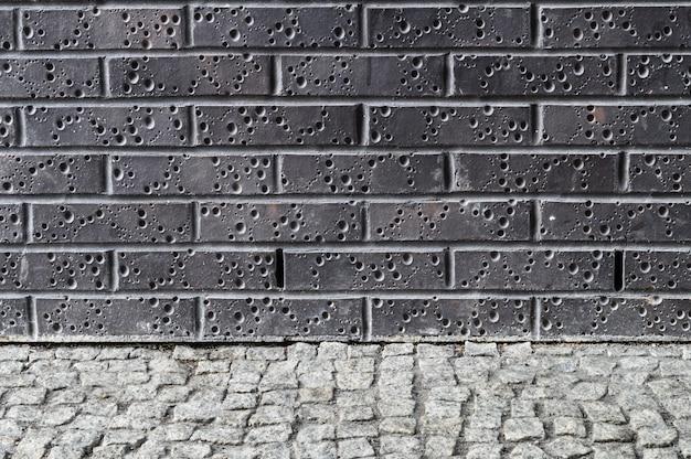 Moderne dunkle backsteinmauer mit grauem pflasterboden