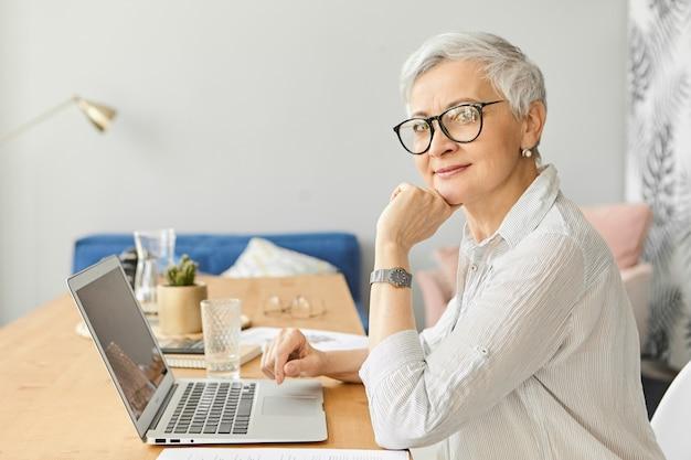 Moderne elektronische geräte, beruf, alter und reife konzept. seitenansicht der attraktiven stilvollen selbständigen frau mittleren alters in gläsern, die vor offenem laptop sitzen und zu hause arbeiten