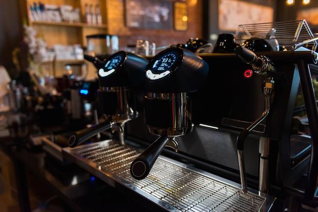 Moderne espressomaschine mit digitaler steuerung in der kaffeestube, dunkler ton