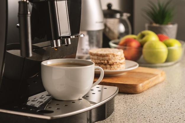 Moderne espressomaschine mit einer tasse im innenraum der küchennahaufnahme.