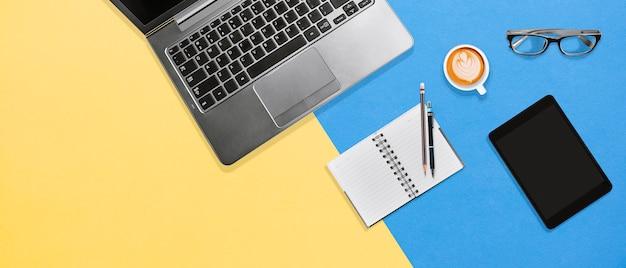 Moderne farbschreibtischtabelle mit laptop, notizbuch, tablette und kaffee mit kopienraum