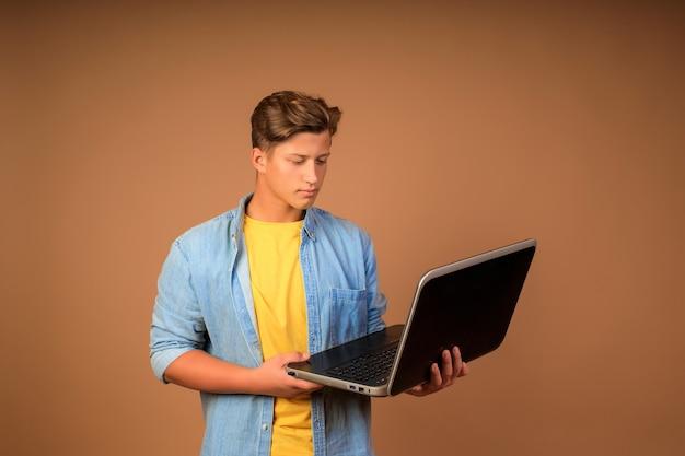 Moderne fernarbeit. porträt eines jungen mannes mit einem laptop in den händen an einer beigen wand