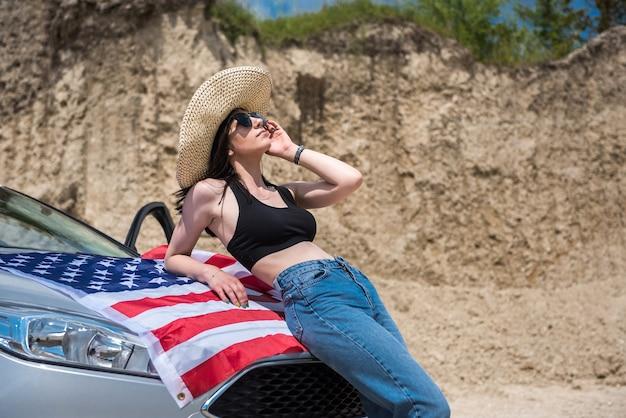 Moderne fotosession hübsche frau mit usa-flagge in der nähe von auto im sandsteinbruch. lebensstil