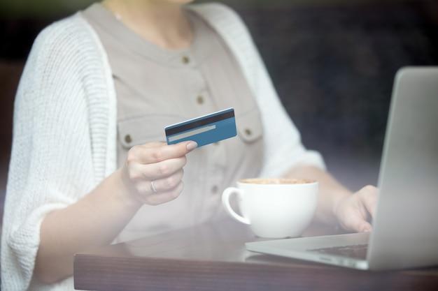 Moderne frau bezahlt online mit kreditkarte. schuss durch fenster