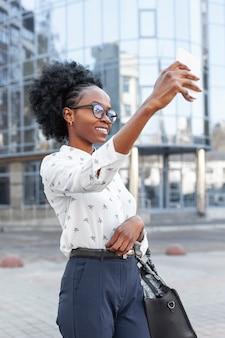 Moderne frau der seitenansicht, die ein selfie nimmt