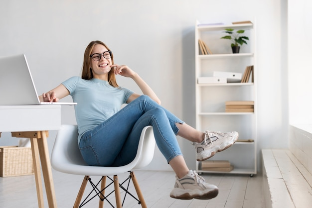 Moderne frau der totalen, die auf ihrem stuhl sich entspannt