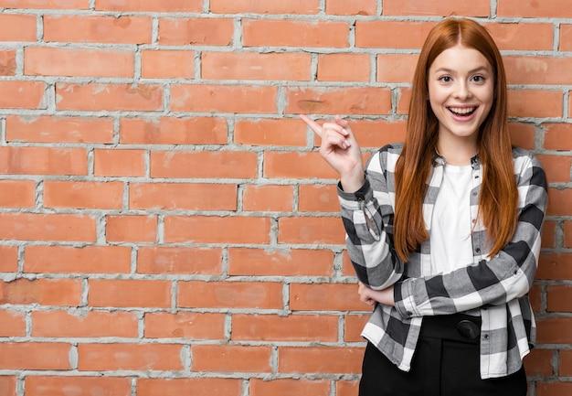 Moderne frau, die auf backsteinmauer zeigt