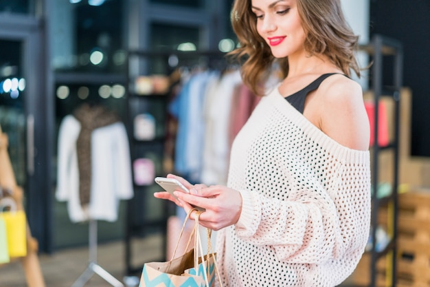 Moderne frau, die das mobiltelefon in der hand hält einkaufstaschen betrachtet