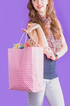Moderne frau, die einkaufstasche voll von eingewickeltem geschenk hält