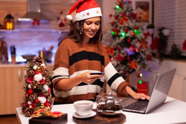 Moderne frau, die geschenke mit kreditkarte bezahlt