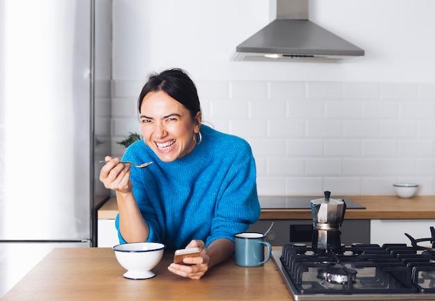 Moderne frau, die in der küche frühstückt