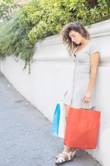 Moderne frau, die mit einkaufstaschen aufwirft