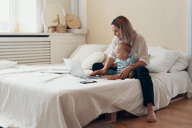 Moderne frau, die mit kind arbeitet. multitasking-, freiberufler- und mutterschaftskonzept