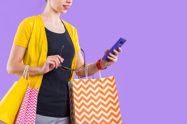 Moderne frau, die mobiltelefon mit dem halten der bunten papiertüte und der brillen verwendet