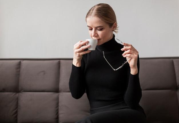 Moderne frau, die tasse kaffee genießt