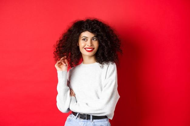 Moderne frau im sweatshirt, spielend mit lockigem haar und beiseite schauend auf leeren raum, stehend auf rotem hintergrund.