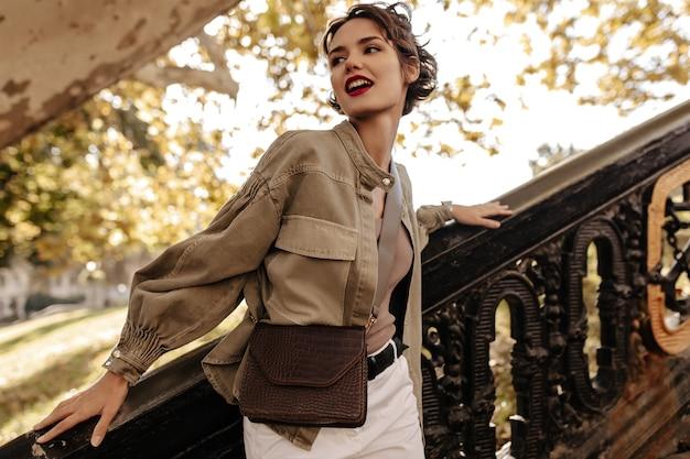 Moderne frau in jeansjacke und weißen hosen, die draußen wegschauen. wellenhaarige frau mit roten lippen mit handtasche, die nahe treppen aufwirft.