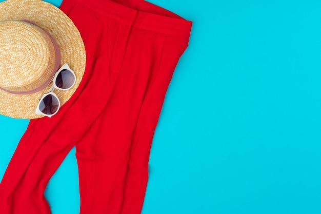 Moderne frau kleidet flatlay auf blauem hintergrund