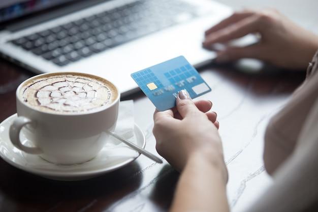 Moderne frau mit kreditkarte für online-zahlung. nahansicht