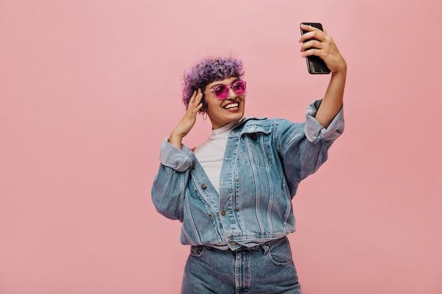 Moderne frau mit lila haaren in der kühlen sonnenbrille macht foto auf rosa. lächelnde dame in weiten hellen kleidern macht selfie.