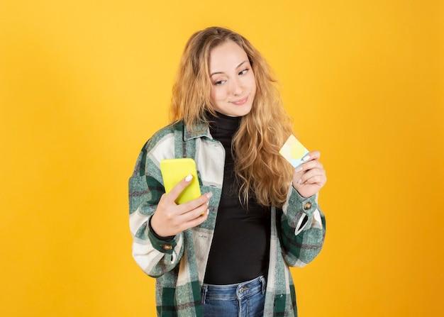 Moderne frau zahlt mit handy und datentelefon