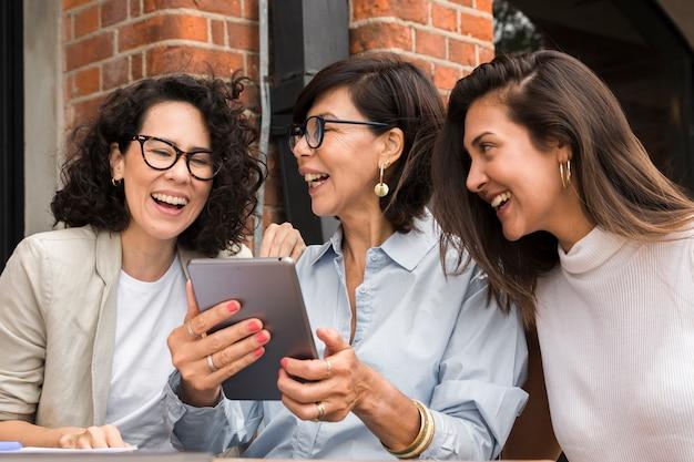 Moderne frauen des smiley, die auf einer tablette schauen