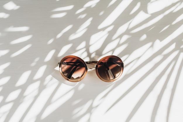 Moderne frauen-sonnenbrille auf weißem tisch mit palmblattschatten