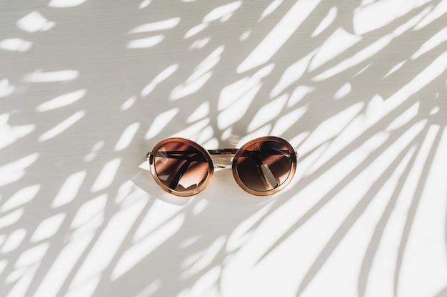 Moderne frauen-sonnenbrille auf weißem tisch mit schatten-schattenschattenbild der grasblätter