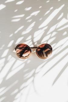 Moderne frauensonnenbrille auf weißem tisch mit gras lässt schattenschattenbild