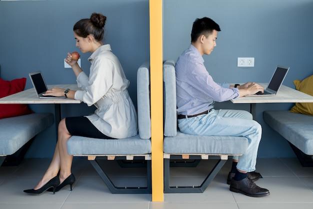 Moderne freiberufler, die laptops im coworking space verwenden