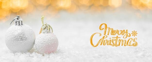 Moderne frohe weihnachtsgrußkarte mit bällen auf dem schnee und verschwommenen lichtern