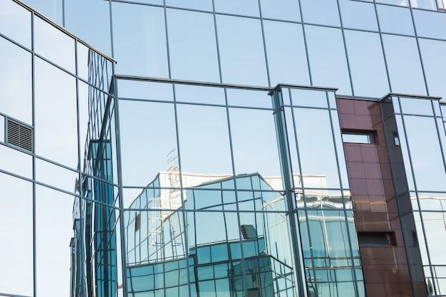 Moderne gebäude, geschäfts- und architekturkonzept - sonnenlicht spiegelt sich im bürogebäude wider.