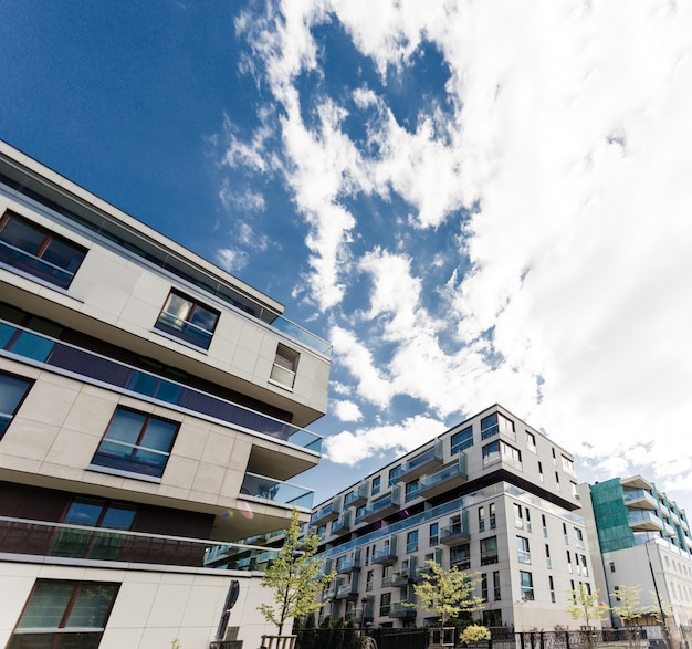 Moderne gebäude. neuer moderner wohnblock im grünen bereich mit blauem himmel