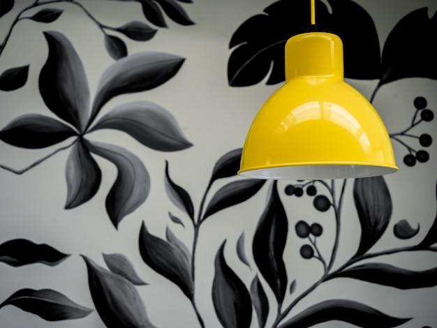 Moderne gelbe deckenleuchte auf tapete, tropische palmblätter im schwarzweiss-farbhintergrund.