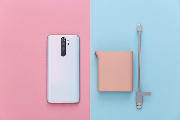 Moderne geräte. smartphone und powerbank auf rosa blauem pastell