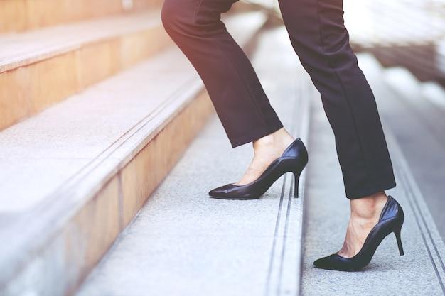 Moderne geschäftsfrau arbeitende frau schließen beine, die die treppe in der modernen stadt in der hauptverkehrszeit hinaufgehen, um im büro eine eile zu arbeiten.
