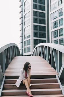 Moderne geschäftsfrau, die auf treppenhaus unter verwendung des handys sitzt