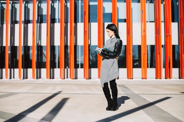 Moderne geschäftsfrau, die draußen smartphone verwendet
