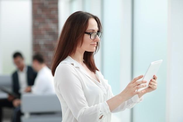 Moderne geschäftsfrau, die eine nachricht auf einem digitalen tablett liest.